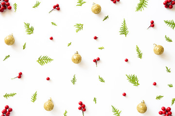 Christmas and New Year's composition. Top view of spruce branches, pine cones, red berries and golden ball on white background.