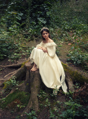 A young, sad princess with very long hair sits on a large stump of an old tree and waits for her prince. The girl has a vintage dress and a diadem. Artistic processing, unusual colors.