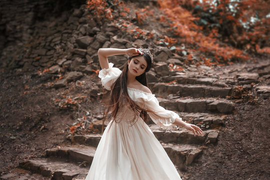 Young princess with very long hair posing against the background of an old stone staircase. The girl has a crystal crown and a white, flying vintage dress. Artistic processing, unusual colors