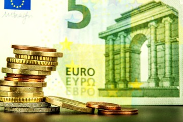 Euro coins on euro banknotes as background. Close-up of several euro coins. Concept of trading on the stock exchange. Euro exchange rate.