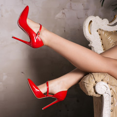 beautiful female legs in red stylish high-heeled shoes are lying on the chair