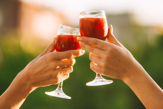 Cheers. Female hands cheering on sunset with red wine fresh sangria glasses with green sunny garden background - female friendship, holidays celebrating and party concept