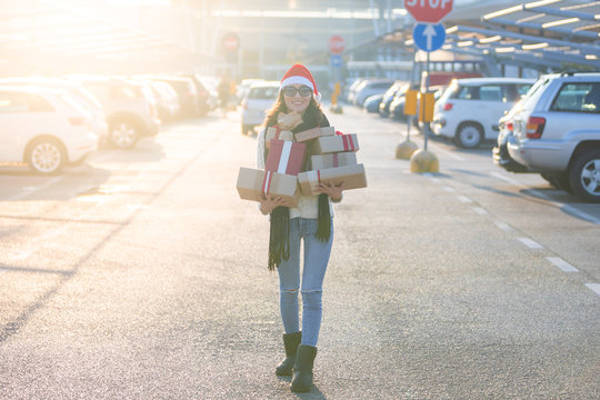 Young woman walking alone in the mall parking to her car, with full hands of Christmas gifts after shopping. Happy smiling girl with a lot of xmas presents and santa's red hat.