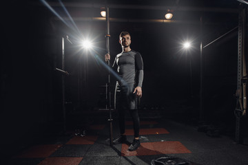 Portrait of man with barbell in hands on dark background. Concept training for workout.