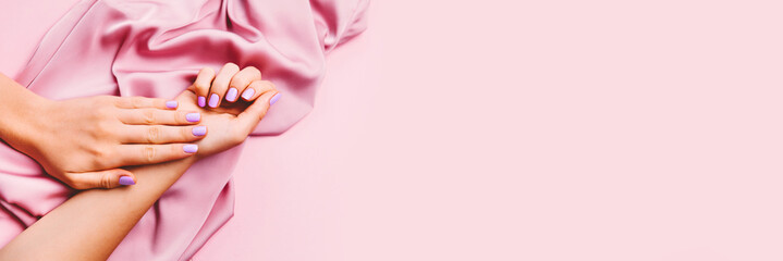 Beautiful woman manicure on creative pink background with silk fabric. Minimalist trend.