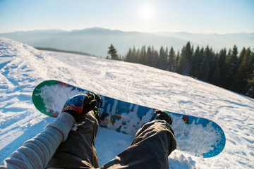 Point of view shot of a female snowboarder lying on the snow on the slope relaxing after riding, enjoying stunning view of winter mountains and sunset POV concept Wall mural