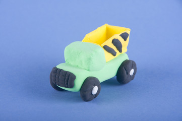 Toy transport. Green, yellow dump truck made of playing clay on purple background