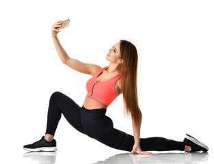Sport woman gymnastics doing stretching fitness exercise workout and make selfie on her cellphone mobile