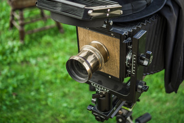 An old camera with legs stands on the street on the green grass. City event