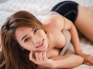 Beautiful asian woman sexy model in sleepwear on bed at home in the morning bedroom.