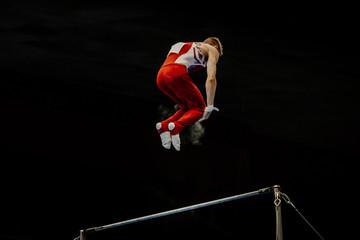 Foto auf Leinwand Gymnastik men gymnast flips dismount in horizontal bars