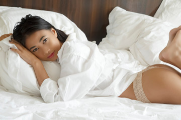 Beautiful Asian woman posing nude on white sheets