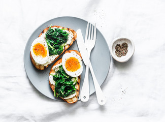 Fried spinach, labne and boiled eggs sandwiches - delicious healthy breakfast or snack on a light background, top view