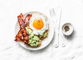 Healthy nutritious breakfast or snack - avocado toast, bacon and fried egg on light background, top view