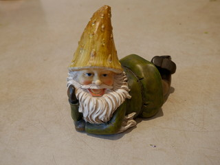 Garden Gnome lies on his stornach and laughs. Close-up.Isolated against neutral background
