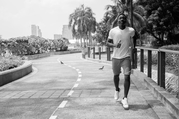 Black and white image of young African man running outdoors in park