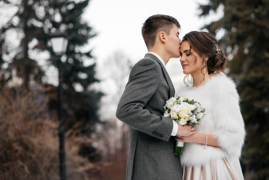 Winter fairy tale. Loving and beautiful bride and groom stand in the winter forest