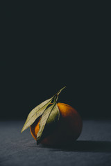 Ripe orange clementine with green leave on the table, photographed in low light