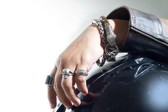 Hand with accessories, standing on helmet. Accessories of the fingers and hands of motorbike riders. Isolated on biker accessories concept.