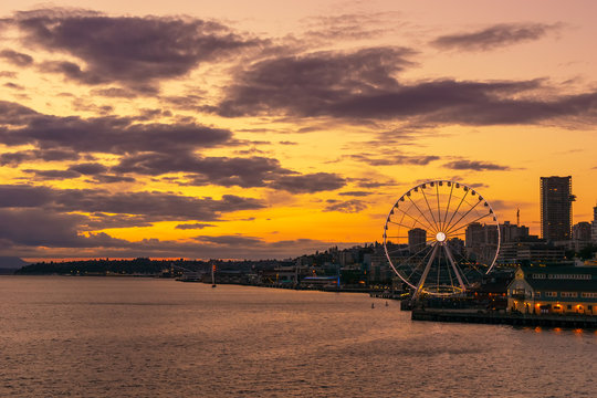 Vibrant and colorful Seattle skyline waterfont with the Great or Ferris Wheel at sunset or dusk from Elliott Bay, Washington state, USA.