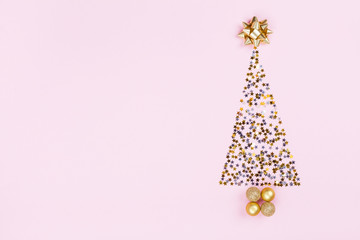 Christmas creative fir tree from confetti stars, serpentine and golden balls on pink background top view. Flat lay..