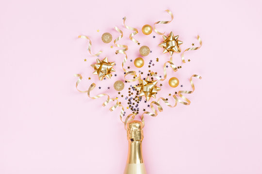 Champagne bottle with christmas decoration from confetti stars, golden balls and party streamers on pink background. Flat lay style. .