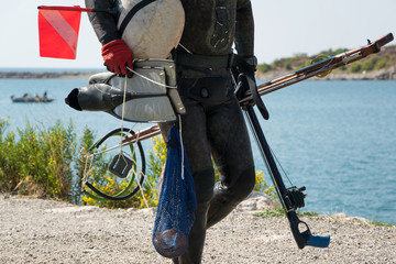 Crop view of scuba diver adult man on a seashore with spearfishing gear (fins, speargun)