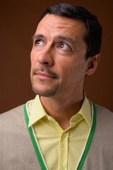 Portrait of handsome man thinking against brown background