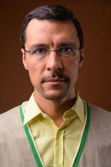 Portrait of handsome man wearing eyeglsses against brown background