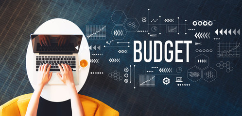 Budget with person using a laptop on a white table