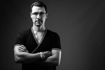 Black and white studio portrait of man wearing eyeglasses