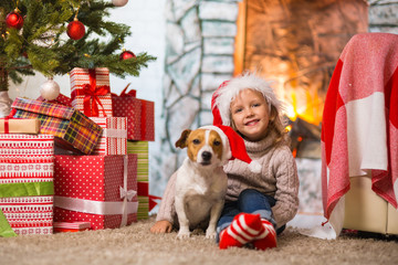 girl child celebrating a happy Christmas at home by the fireplace with a pet dog Jack Russell