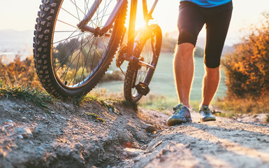 Young cyclist man pushing a mountain bike up the hill close up image. Active adventure travel on bicycle.