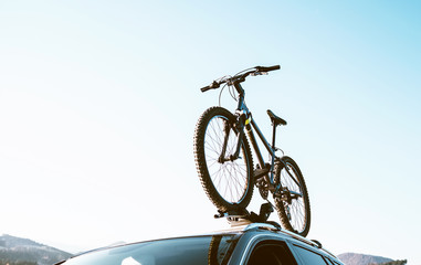Mountain Bicycle fixed with Roof Mounted Bike Carriers instaled on white Auto roof travel concept image
