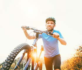 Young smiling man pushing a mountain bike up the hill. Active adventure travel on bicycle.