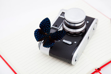 A blue morpho butterfly and a camera lie on an open notebook. Explore butterflies, ethnology