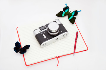 Two blue morpho butterfly and a camera lie on an open notebook and a ballpoint pen lies next to it. Explore butterflies, ethnology