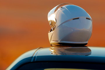 A Racing Helmet Sitting On Top Of A Car In The Early Morning Sun
