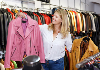 blonde choosing leather jacket on racks