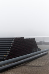 Tubes & Pipes Stacked Perfectly In Foggy Storage Yard