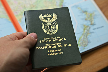 Photo sur Aluminium Amérique du Sud A South African travel passport in a man's hand with map in the background. This image can be used to represent emigration to New Zealand. This image has selective focusing.