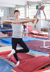 Sporty man asian gymnast during workout in gym,  woman on background