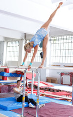 Couple doing exercises on parallel bars