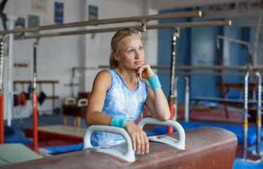 Woman posing near gymnastic equipment