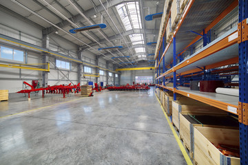 Large, spacious assembly shop. High storage racks with wooden boxes