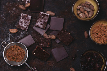 Chopped chocolate, cocoa beans, cocoa powder on rusty metal background. Toned. Haze effect