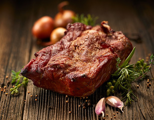 Smoked meats,  smoked pork loin on a wooden  table with addition of fresh  herbs and aromatic spices.  Traditional smoked meat smoked in apple wood and beech  wood. Natural product from organic farm