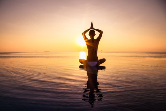 Woman has meditation and Yoga at infinity pool during sunset.