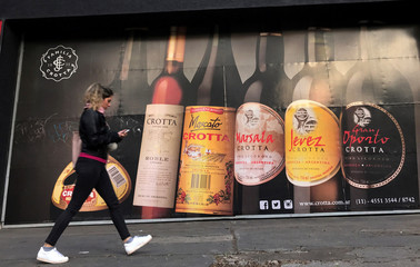 A woman walks past a billboard advertising wine outside a beverage wearhouse in Buenos Aires