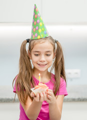 Smiling girl  in party hat with birthday cupcake